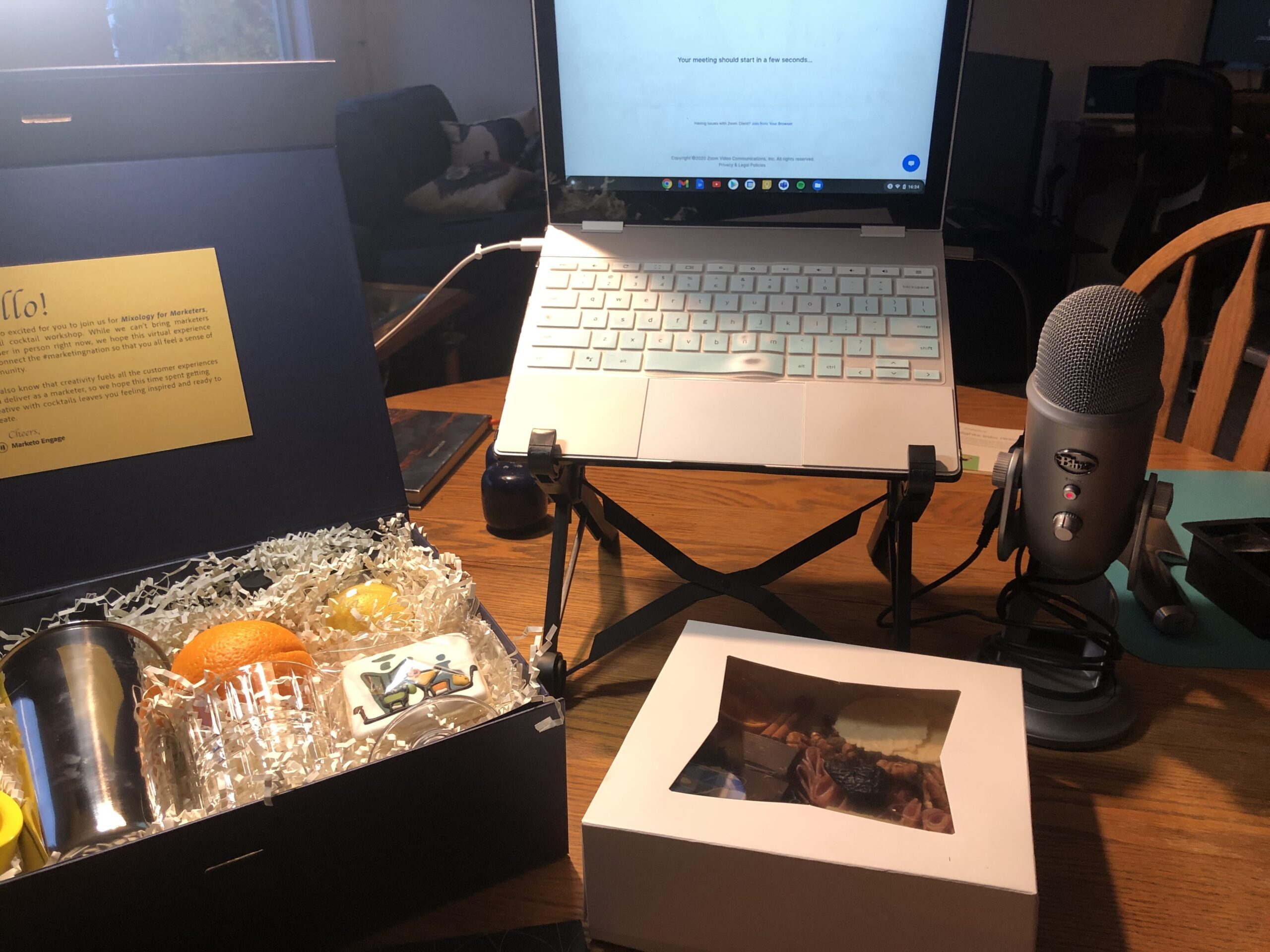 virtual event swag box with cocktail kit, charcuterie snacks, laptop and microphone